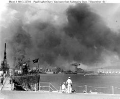 Pearl Harbor Attack, 7 December 1941 View looking toward the Navy Yard from the Submarine Base during the attack. Submarine in the left foreground is USS Narwhal (SS-167). In the distance are several cruisers, with large cranes and 1010 Dock in the right center. Note Sailors in the center foreground, wearing web pistol belts with their white uniforms. Official U.S. Navy Photograph, National Archives Collection.