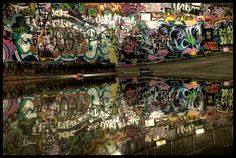 A swirl of competing graffiti tags reflected in the water on Leake Street, London.