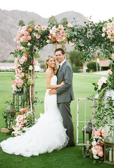 Brides.com: . A classic altar covered in greenery and pink roses, created by Elegant by Design.