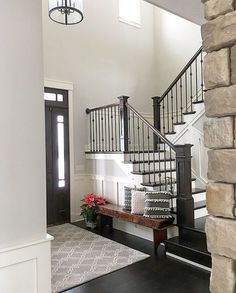 Neutral modern farmhouse foyer with wainscoting, stained and painted stairs | See this Instagram photo by @farmhouseredefined