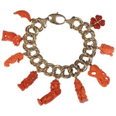 Designed as a line of double oval curb links with attached nine coral charms depicting an half...