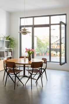 Bright dining room with concrete floor, vintage chairs and table in the home of architect: Nicholas Petillon. Photo by Bart Kiggen.
