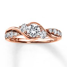 A round diamond, nestled by two additional diamonds, forms the brilliant center of this lovely engagement ring for her. A wave of even more diamonds flows under the center, while 14K rose gold swirls frame the center to complete the look. The ring has a total diamond weight of 7/8 carat. Diamond Total Carat Weight may range from .83 - .94 carats.