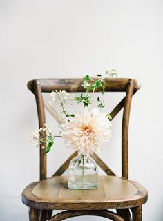 Five simple bud vases with café au lait dahlias, burgundy astilbe and sage will be sprinkled around the client's picture frames with cut glass votives.