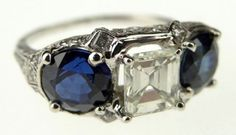 Lady's 1.21 Carat Emerald Cut Diamond, 3.19 Total Weight Two (2) Round Brilliant Cut Gem Quality Sapphire and Platinum Ring. Sapphires with Vivid Blue Saturation of Color and VS Clarity. Diamonds K Color, VS Clarity with Very Good Polish and Symmetry