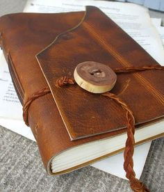Large leather journal made from thick chestnut brown leather. It wraps closed and is secured with a handmade mimosa wood button and braided leather tie. 288 pages of creamy linen paper, handstitched into the spine with chocolate waxed linen thread. Measures about 6 x 9 inches. By Awaken Journaling, Etsy