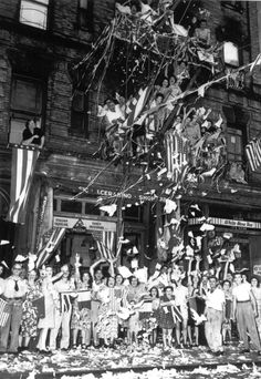 A jubilant crowd of American Italians are seen as they wave flags and toss papers in the air while celebrating Japan's unconditional surrender in their neighborhood in New York City. August 14, 1945.