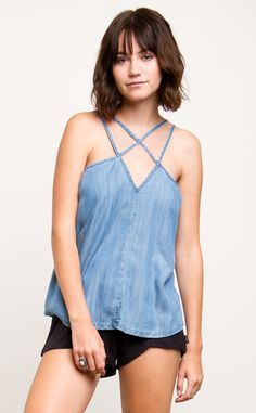 The RVCA Haze is a chambray woven tank top with strapping details at the front and back.  The tank has a RVCA flag label at the wearer's left side seam.