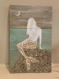 Size: 10 1/2 x 16 1/2  Hand painted Mermaid with tail decorated in collected seashells, sitting upon a rock of crushed seashells all from
