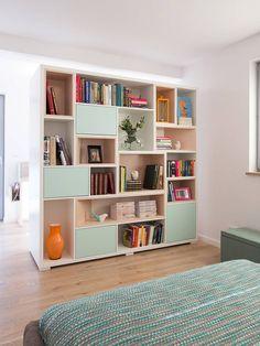 Regał na książki to nietypowy mebel do sypialni. Ten mebel poza otwartymi półkami, ma też schowki umieszczone za miętowymi frontami. Pod kolor drzwiczek otwieranych na docisk dobrano obitą tkaniną skrzynię i narzutę na łóżko.