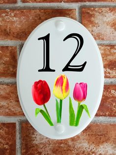 A range of pottery style house plaques feature prints of original artwork from our own sign artists. Hand cast in cultured marble these number plates are weatherproof outdoors. House Plaques, House Number Plaque, House Numbers, Tulips Flowers, Floral Motif, Original Artwork, Decorative Plates, Pottery, Prints