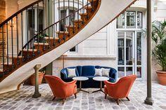 Sous un splendide escalier en spirale du XVIIIème siècle dans le lobby, des sofas colorés - The Hoxton Paris