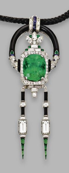 An Art Deco emerald, diamond, onyx and sapphire pendant-necklace, Mauboussin, circa 1925. Centring a cushion-shaped emerald weighing approximately 25.50 carats. Mounted in platinum, signed Mauboussin. Necklace 19 inches long. #Mauboussin #ArtDeco #pendant