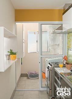 Um piso de porcelanato cinza aplicado na cozinha se repete na área de serviço, proporcionando a sensação de continuidade entre os espaços.  Cores da parede  Colheita Dourada Ref. 20YY 28/613 e Meditação Ref. 30YY 69/048 - Coral  Projeto do arquiteto Douglas Honma