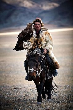A mongolian hunter on a riding horse armed with a Golden Eagle.