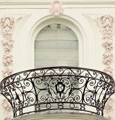 white arched window with black circular wrought iron balcony in Paris, France