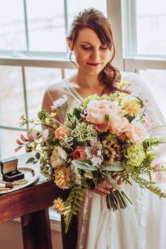 Dreaming of a romantic vintage style wedding? Take your bridal flowers with you and leave stress behind with a high-end faux flower bouquet. You'll be able to see it before the wedding, enjoy it on the big day, and hold onto it as a keepsake. Created in a loose clutch style, this lifelike, Pinterest-worthy Garden Flower Bouquet is absolutely stunning! * The soft palette of pink, peach, buttery yellow and lavender is accented with fresh green and loads of texture* Features faux garden roses, ranu