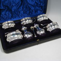 Antique Victorian sterling silver Art Nouveau seven-piece condiment service with spoons, all in original satin and velvet-lined presentation box. Consisting of four open salt cellars with gold-gilt interiors, two pepper pots with pull-off lids, and a single mustard pot with hinged lid and gold-gilt interior, together with four salt spoons and one mustard spoon with gold-gilt bowls. All made by James Round of Sheffield in 1897 (the condiment spoons are made by James Round in 1901). Length of…