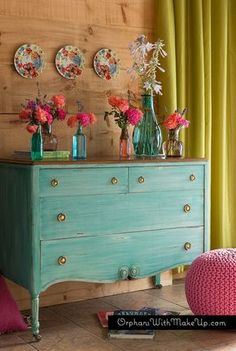 Fun, bright, bohemian aqua painted dresser with Pioneer Woman's floral plates and bright garden flowers. The green curtains and pink pouf are great contrasts!