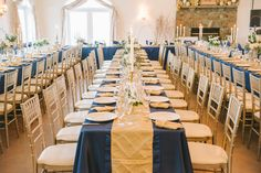 Jof Panlaqui Photography of a White Button Events wedding, Navy, tablecloths with champagne gold pintuck runners and a crinkled taffeta runner that was used to give more depth, both of texture and color on the tables.   Also the tables were not decorated exactly the same to keep it from being monotonous it had a beautiful flow to each intimate banquet/family style seating row.