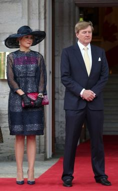 The queens wears a lace dress by Natan. Click on the image to see more looks.