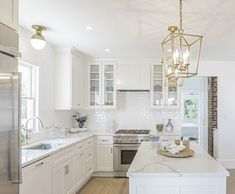 This classic white kitchen has painted shaker cabinetry and quartz countertops. Warming the space are wood floors and accents of gold and silver. White Coastal Kitchen, Small White Kitchens, White Shaker Kitchen, Classic White Kitchen, Kitchen And Bath Design, Modern Kitchen Design, Home Decor Kitchen, Home Kitchens, White Kitchen Designs