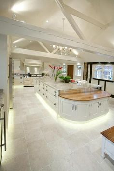 Luxury large white kitchen.  open ceiling idea for ranch home, island with raised marble and lower curved wood and under cabinet  lighting detail.