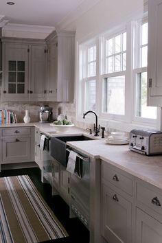 kitchens - gray kitchen cabinets stainless steel apron sink twin dishwashers oil-rubbed bronze faucet green blue striped kitchen runner  Beautiful