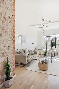 bright living room with light oak wood floors, exposed brick walls, and clean white walls and ceiling