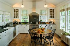 white glass-front kitchen cabinets, black granite countertops, cabinet pulls, farmhouse sink, wood floors