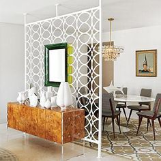 Jonathan Adler created this glam midcentury modern dining room.  He shielded the quieter spot from the lively great room with an architectural screen affixed with two back-to-back Philippe Starck mirrors. Coastalliving.com