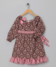 This lively dress shows off a combination of prints on comfy cotton. It's ready for any kind of play with puffy sleeves and a peasant-inspired top with an elastic neckline. A matching bow tags along for fun.