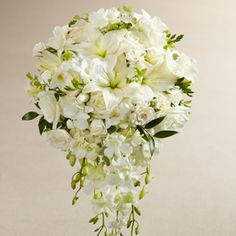 white blooms including: Dendrobium Orchids, roses, Asiatic Lilies, freesia, spray roses, and mini hydrangea are offset by beautiful lush greens and arranged in a cascade fashion