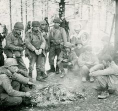 Soldiers of the US Army huddle around a campfire in the bitter Belgian winter during the Battle of the Bulge #WW2 #History