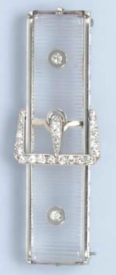 AN ART DECO ROCK CRYSTAL AND DIAMOND BROOCH BY BLACK STARR & FROST CIRCA 1925. The rock crystal plaque with engraved banding enhanced by a central old European-cut diamond buckle motif further enhanced by diamond collet accents mounted in platinum signed B.S.& F. #ArtDeco #BlackStarrFrost #brooch