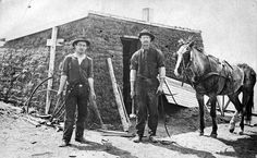 1910 Photograph of Neil McCrea and George Shenton and a harnessed horse in front of a sod shack. One man is holding a sledge hammer and the other a curved pick.