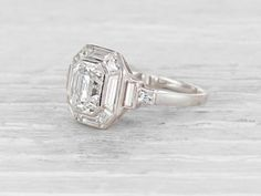 French Art Deco engagement ring set with a step emerald-cut diamond weighing approximately 1.65 carats with EGL certificate stating the diamond is F-G color/VS1 clarity. Framed by 12 baguette-cut diamonds weighing approximately 0.90 carat total. Set in platinum. With French marks.Circa 1925 This is a spectacular example of period French jewelry. Crisp, stylish and rare.Learn more about Art Deco rings Diamond and gold mining has caused devastation in areassuch as Africa, wreaking havo...