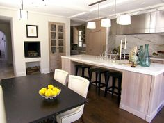 This great little dining area/kitchen features easy to clean faux leather, washed oak, Calcutta marble and stainless steel.  I love that there is bar seating as well as a dining table!  SErves all functions.  (Plus, let's acknowledge that awesome wood-burning fireplace--how cool!)