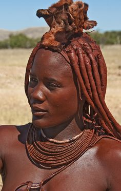 The Himba people are an ethnic group of about 20,000 to 50,000 people living in northern Namibia, in the Kaokoland region. They are a nomadic, pastoral people and they breed cattle and goats. They wear little clothing, but the women are famous for covering themselves with otjize, a mixture of butter fat and ochre, possibly to protect themselves from the sun. The mixture gives their skins a reddish tinge. This symbolizes earth's rich red color and the blood that symbolizes life, and is consist...