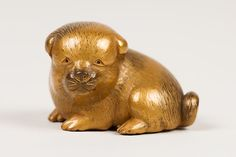 Netsuke of Seated Puppy with Short Curled Tail Artist: Norizane (Japanese) Date: first half of the 19th century Culture: Japan Medium: Wood, gold lacquer mottled with black; black lacquer eyes Dimensions: H. 1 1/8 in. (2.9 cm); W. 1 in. (2.5 cm); L. 1 1/2 in. (3.8 cm)
