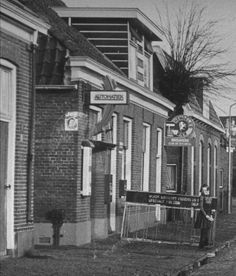Ook de parkeerplaats bij Cafe Restaurant de Marke wordt bij de plannen betrokken, zodat deze ook volledig wordt vernieuwd. Super natuurlijk.  In februari 1949 startten Gerrit en Riek Brouwer met de automatiekhal in een verbouwde slaapkamer. Op de foto is de situatie aan de Vossenbeldsstraat te zien rondom 1950. We zien het woonhuis van de familie Brouwer met de automatiek. De boerderij links is afgebroken en staat op de plek van de huidige parkeerplaats.