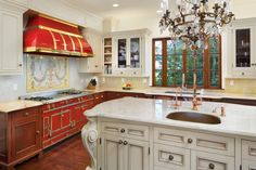The kitchen has a La Cornue stove and a large center island with seating while overlooking the gorgeous grounds.
