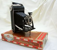 A vintage camera my father own. It's a Kodak Junior There is still cigars in the old box. Old Cameras, Daily Photo, The World's Greatest, Chanel Boy Bag, Cigar, More Fun, Photographs, Shoulder Bag, Box