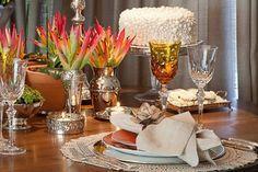 mesa posta com decoração em bege, branco e laranja com detalhes em renda e bolo em pérolas.