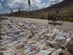 """Dec 3 Inquirer News """"'Yolanda' death toll at 5,680; 1,779 still missing"""" - Typhoon Yolanda survivors pass by hundreds of victims lying in body bags on the roadside until forensic experts can register and bury them in a mass grave outside of Tacloban, Philippines on  Nov. 19, 2013"""