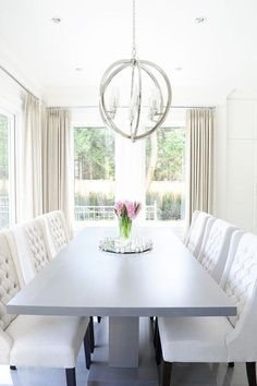 Chic dining room features a gray pedestal dining table lined with white wingback dining chairs illuminated by a polished nickel sphere pendant surrounded by windows dressed in cream curtains.
