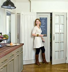 In this cottage kitchen, pegboard hides an unsightly water heater and creates space for the grocery list. Brooms and other cleaning supplies hang on the other side.