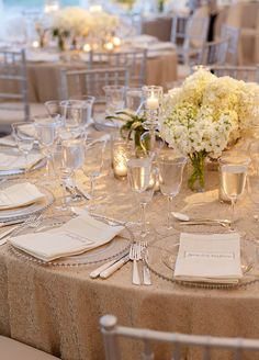 Beautiful all white centerpieces on cream color textured table linen.