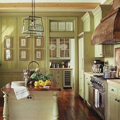 This pretty green glazed kitchen works beautifully with its graceful design and beautiful sculpted wood floors with low sheen, a nice touch..also love how they did the paneling in the same color, very pretty