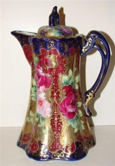 PORCELAIN CHOCOLATE POT. Cobalt blue, maroon, and gilt jeweled decoration with hand painted red and pink roses.